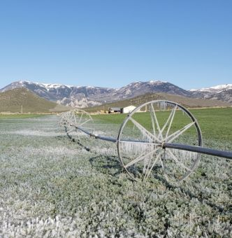 frozen field and irrigation wheels with mountains in the background