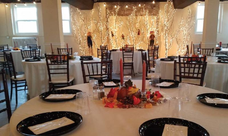 Fully set up event space with tables, seating, dinnerware, and decor