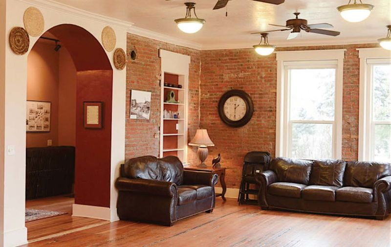 Bright living space with exposed red brick walls, arched doorway, built-in bookshelf, and leather seating