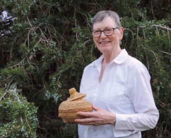 Deanna Cole holds a native basket she collected while teaching in remote villages in Alaska.
