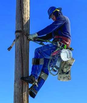 Journeyman Lineman Billy Fullmer climbs a pole to change out a contract light on Raft River Electric lines. PHOTO BY JERAMY LOGUE