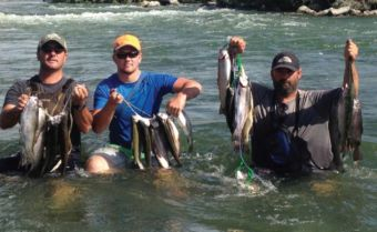 From left, Shane, son Sy and brother Bryce show their catch while waist-deep in the Snake River.