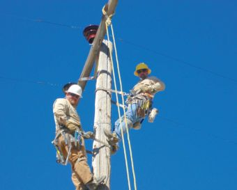 Lineman Justin Bair, left, and Hutch work on a pole. Photo courtesy of Raft River Electric Co-op, Inc.