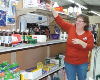 Sherry Southern stocks Malta Farm & Ranch Supply shelves with livestock medication, hardware supplies, gloves and food.