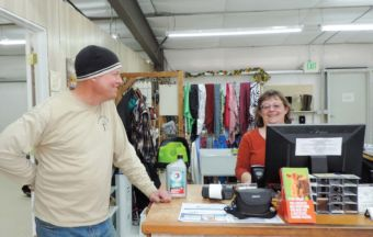 Tim Tracy drops in for a quart of oil for his truck. Standing at a cash register with Sherry.