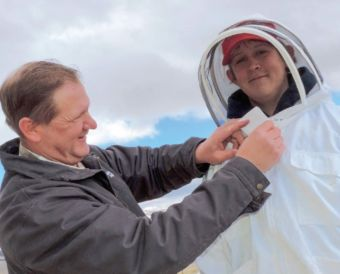 Before checking on hives, Zane gets into protective clothing with help from his dad, Chad.